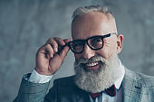 Close up portrait of cheerful affable stylish trendy rich intelligent smart dreamy professional elegant excited elite luxurious old-fashioned grandpa trying on new glasses isolated on grey background