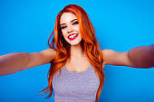 Portrait of stylish funny happy carefree girl with ginger hair,cute face and big breast make selfie photo and laugh while standing on blue background