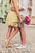 legs of loving hugging couples on the pavement with flowers