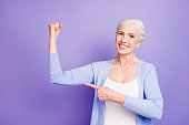 Strength concept. Beautiful nice cheerful smiling gray-haired old lady wearing casual, showing pointing with finger at her arm. Isolated over pastel violet purple background
