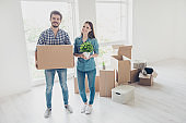 New life, new start, new home for a young family. What a joy! Happy cheerful lovers are unpacking in a new apartment, standing in a casual wear