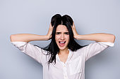 Overworked furious stressed young  woman in rage touching head and screaming with open mouth  in formalwear