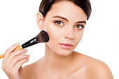 Sensual young woman on isolated white background  applying blusher on her cheekbones using make-up brush