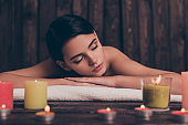 Beautiful pretty relaxed young woman laying in spa salon with closed eyes
