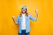 Yes! Lucky young hipster man isolated over yellow background, happy man wearing glasses and hat acts like he won something with raised hands, emotion, success, gesture and people concept