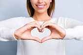 Cropped portrait of smiling woman in white outfit showing focused love symbol heart figure with fingers isolated on grey background