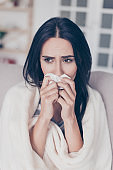 Beautiful sad depressed young woman touches her nose with napkin. She sits with coverlet on sofa at home