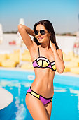 Sexy slim brunette gorgeous girl in sun glasses is standing by the swimming pool in colorful swim suit, so hot and attractive, figure is ideal, skin is so perfect and healthy, shining and smooth