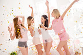 Cheerful, sexy, pretty, charming, funky girls in rain of colorful stars, confetti enjoying meeting indoor, drinking alcohol, dancing, shouting, screaming, laughing with raised arms, standing near bed