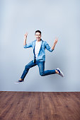 Freedom, carefree, fun, summer mood. Excited brunete guy is jumping and showing peace signs. He is in casual jeans outfit and gumshoes