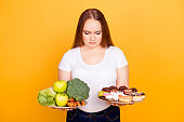 Confused sad upset woman wearing white tshirt can't make a choice between healthy and unhealthy food, she is holding two plates on her hands, isolated on yellow background