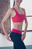 Close up photo of perfect fit slim woman's belly. Bodybuilder is wearing stylish sportswear ans smiling