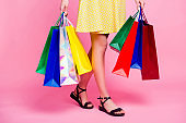 Cropped portrait of woman's slim sexy legs going from shopping having a lot of colorful bags in hands isolated on pink background, day of big sales