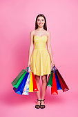 Full length, size, fullbody portrait of pretty, brunette, lovely, cute, nice, positive woman in yellow dress having many colorful shopping bags in hands, standing over pink background