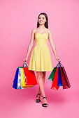 Vertical full-size full-length portrait of charming beautiful cute romantic perfect attractive pretty woman carrying many colorful bags with apparel isolated on background short dotted dress sandals