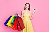 When you are stressed just go shopping! Portrait of delightful excited joyful cheerful attractive pretty in yellow dotted dress woman recommending to pay using credit card isolated on pink background