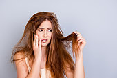 Sad young cute girl is looking at her damaged hair with shock, standing isolated on a pure background, touching her face