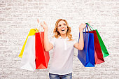 Happy woman with paperbags doing shopping in the mall