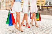 Close up photo of beautiful women's legs and shopping bags