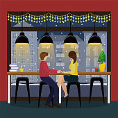 Couple in love with champagne at the bar counter at the panoramic window in the coffee house. Christmas interior in the cafe. Romantic date.