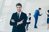 Portrait of happy young manager in office with crossed hands
