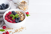 Smoothie bowl with yogurt, fresh aromatic berries and cereal. Close up view