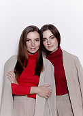 Two beautiful young women sisters look happy confident wearing beige blazers pants red turtle neck Fashion models friends studio portrait