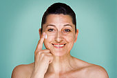 Woman portrait at her 50s before and after applying face cream