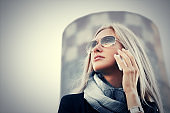 Blond fashion business woman in sunglasses talking on mobile phone outdoor