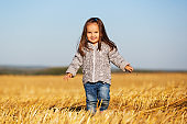 Happy two year girl walking in a summer harvested field
