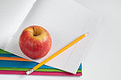 Pencil and apple on school notebook