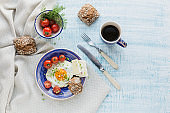 Coffee cup, one egg, cheese and cherry tomatoes for healthy breakfast.