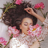 Young woman lies among peonies