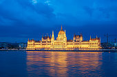 Budapest Parliament Building with view of Danube River at night in Hungary