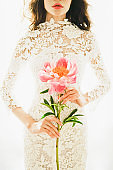 Woman in white lace dress with pink peony