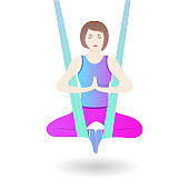 A girl hangs in a hammock in the lotus position. A woman practices asana from aerial yoga.