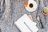 Home workplace with coffee cup on knitted plaid