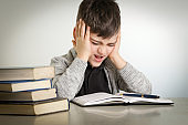 Studio portrait of young boy struggling with his homework - learning difficulties concept