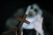 frightening evil nun screaming in front of a cross
