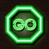 Green glowing neon road sign on brick wall with big bright letters GO