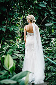 Woman back stand in the Botanical green garden full of greenery. Portrait attractive blonde bride standing in a wedding dress on the background of greenery.