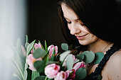 Beautiful girl in the dress with bouquet of flowers tulips in hands on a light background near windows at the home. Happy Women's Day.