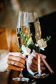 The bride and groom hold glasses of champagne in their hands. Glass decorated with flowers and greenery on the background newlyweds. close up. Wedding ceremony.
