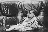 Cute baby covered with towel sitting on parents bed, couch, after bath or shower. Clean dry child in bedroom. Concept bathing and washing of little kids. Children hygiene. Black and white photo.