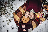 Man and girl is lying on a blanket at the winter picnic on the Valentines Day in a snowy park, forest. Basket with cookies, fruits, mulled wine, hot tea, coffee. Top view, flat lay.
