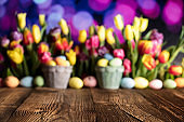 Easter eggs. Colorful tulips. Rustic wooden table. Shallow depth of focus. Bokeh background. Place for typography. Easter theme.