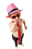 Little boy in tie, sunglasses, and hat is dancing, isolated on white. Little cute cheerful kid is dancing on white background.