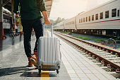 Young tourist man walking drag luggage. other hand holding the map and walking to the train station.Travel concept.