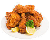 fried chicken with lemon and parsley on a white plate