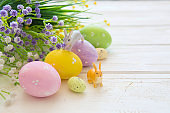 Easter eggs and flowers decoration on rustic wooden background. Vintage style toned picture. Rabbits toys